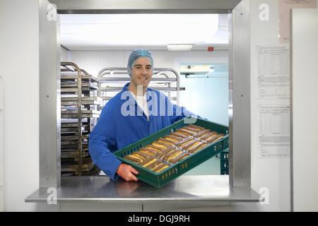 Baker Holding Tablett mit frisch gebackenen Schokoladen Eclairs in kleine Bäckerei - Stockfoto