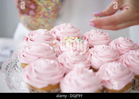 Frau mit Zucker Streusel Muffins dekorieren - Stockfoto