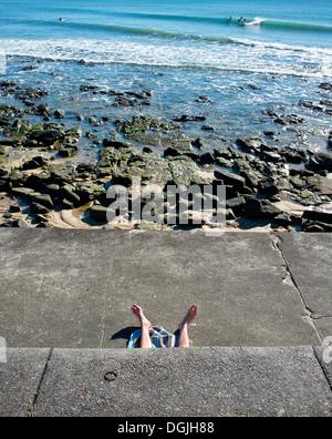 Die Beine der Sonnenanbeter in Alexandra Headland in Queensland. - Stockfoto