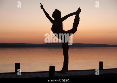 Silhouette einer Frau, die gegen das Licht der Abendsonne, Yoga zu praktizieren, Steinhuder Meer, Steinhuder Meer, - Stockfoto