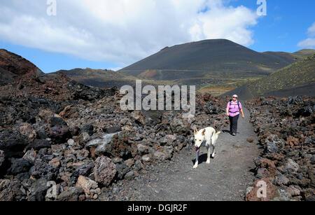 Frau zu Fuß mit einem Hund auf La Palma vor San Antonio Volcano, Kanarische Inseln, Spanien, Europa, PublicGround - Stockfoto