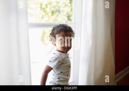 Kleinkind stehen neben Fenster - Stockfoto