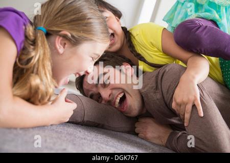 Mädchen kitzeln Vater - Stockfoto