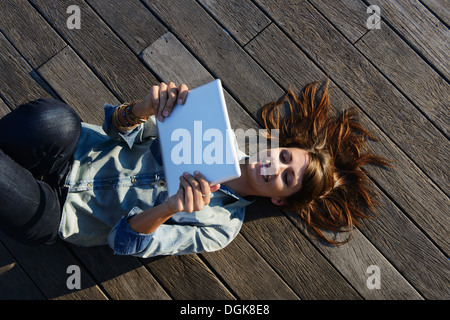 Junge Frau liegt auf Holzbrettern mit digital-Tablette - Stockfoto