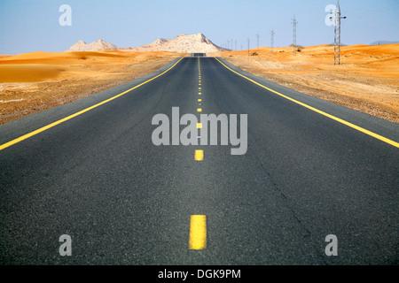 Eine scheinbar endlose Straße in der Wüste von Dubai. - Stockfoto