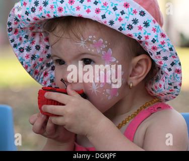 ein junges Mädchen genießen einen Schokoladen cupcake - Stockfoto
