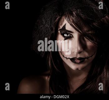 Furchterregende Hexe Porträt isoliert auf schwarzem Hintergrund, attraktive Frau mit unheimlich Make-up, Halloween - Stockfoto