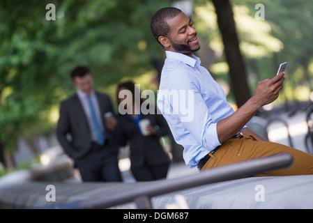 Sommer in der Stadt. Ein junger Mann in einem grauen Anzug und blaue Krawatte zu Fuß mit einer Frau in einem Anzug. - Stockfoto