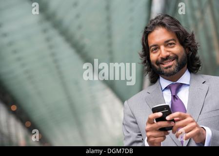 Business-Leute. Ein Mann im Anzug mit einem Vollbart und lockiges Haar. Sein Telefon benutzen. - Stockfoto