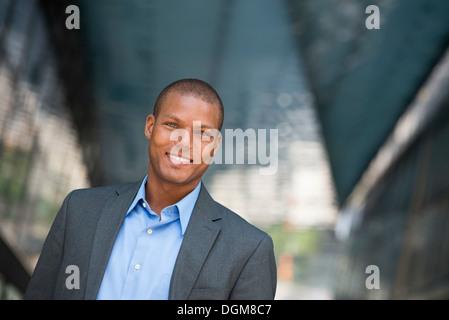Ein Geschäftsmann im Anzug, mit Hemdkragen aufgeknöpft. In einer New-York-City-Straße. - Stockfoto