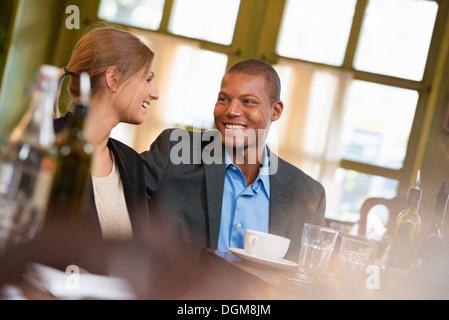 Ein paar, ein Geschäftsmann und Geschäftsfrau in einem Coffee-Shop oder Café, nebeneinander sitzen. Eine Besprechung - Stockfoto