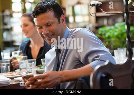 Business-Leute. Drei Menschen an einem Cafétisch, von denen ihr Telefon überprüft wird. - Stockfoto