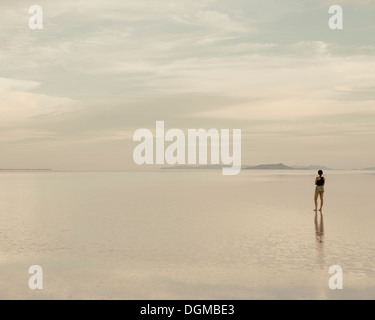 Eine Frau stand auf den überfluteten Bonneville Salt Flats in der Abenddämmerung. Reflexionen im seichten Wasser. - Stockfoto