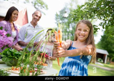 Familienfest. Ein Tisch gedeckt mit Salaten und frischem Obst und Gemüse Kind hält sich frisch gepflückten Karotten. - Stockfoto