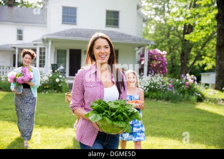 Familienfest. Eltern und Kinder, die Blumen, frisch gepflückten Gemüse und Obst. Vorbereitung für eine Party. - Stockfoto