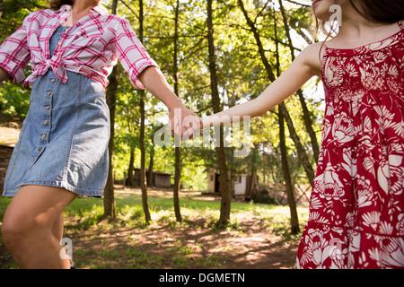 Eine Frau und ein junges Mädchen Hand in Hand und unter den Bäumen entlang laufen. - Stockfoto
