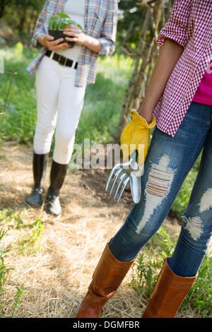 Zwei junge Mädchen in Arbeitskleidung in Gummihandschuhe Gartengeräte hält, und hält eine Pflanze in einen Topf. - Stockfoto