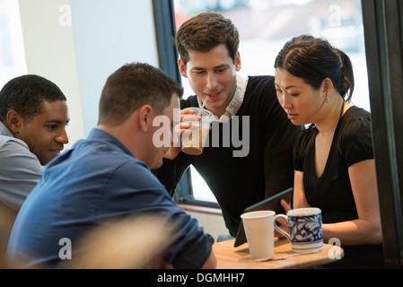 Eine Gruppe von Menschen an einem Tisch in einem Café sitzen. Blick auf den Bildschirm von einem digital-Tablette. - Stockfoto