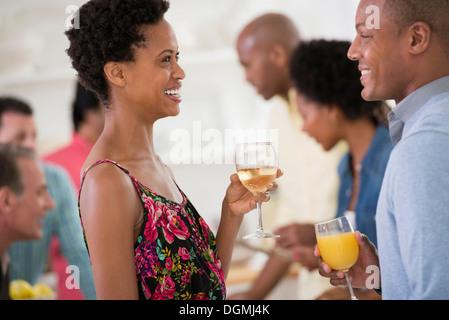 Networking Party oder informelle Veranstaltung. Ein Mann und eine Frau, mit einer Menge um sie herum. - Stockfoto