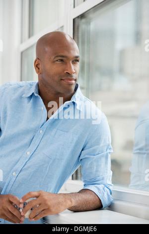 Business-Leute. Ein Mann mit einem Glas Wein aus dem Fenster. - Stockfoto
