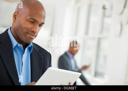 Business-Leute. Ein Mann im Anzug mit einem digitalen Tablet. - Stockfoto