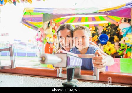 USA, Utah, Salt Lake City, Mutter und Sohn (4-5) spielt mit Wasserpistole im Vergnügungspark - Stockfoto