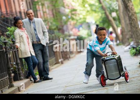 Ein kleiner Junge spielt mit einem alten altmodischen Spielzeugauto auf Rädern auf einer Stadtstraße. Ein paar auf - Stockfoto