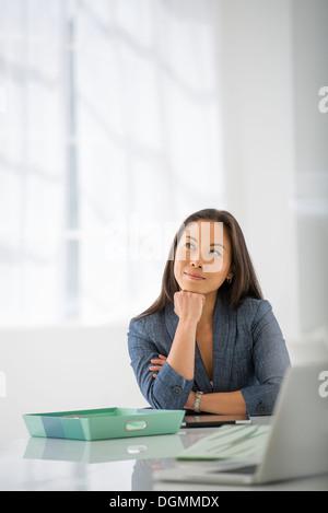 Geschäft. Eine Frau sitzen entspannend, mit ihr Kinn in die Hand.