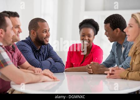Büro. Eine Gruppe von vier Personen, zwei Männer und zwei Frauen sitzen reden.