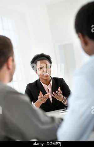 Büroeinrichtung. Drei Personen sitzen um einen Tisch bei einem Geschäftstreffen. - Stockfoto