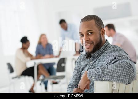 Büroeinrichtung. Treffen. Eine Person, die auf der Suche über die Schulter und von der Gruppe entfernt. - Stockfoto
