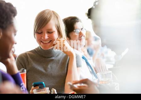 Leben in der Stadt. Eine Gruppe von Menschen in einem Café, überprüfen ihre Smartphones. - Stockfoto