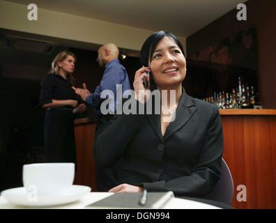Eine junge Frau sitzt in einer Hotelbar auf ein Handy zu sprechen - Stockfoto