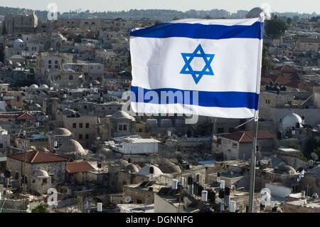 Jeruslaem, Israel. 23. Oktober 2013. Die israelische Flagge Wellen im Vordergrund über die Dächer von muslimischen - Stockfoto