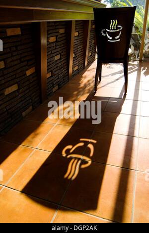 Stuhl mit Kaffee-Logo und lange Schatten - Stockfoto