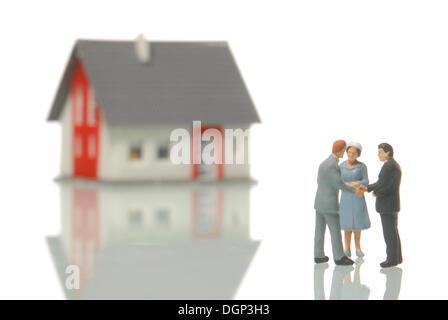 Paar ein Haus aus einen Grundstücksmakler, Figuren, ein unscharfes Haus im Rücken, symbolisches Bild für den Immobilien - Stockfoto