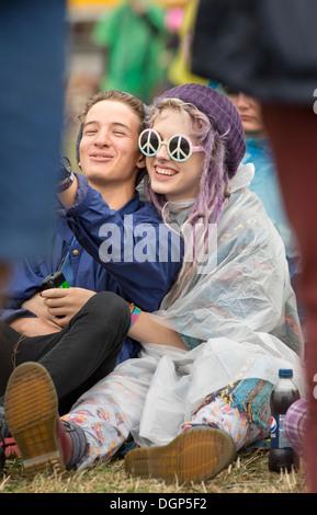 Das Reading Festival - ein Mädchen in einem Plastik Poncho mit CND Sonnenbrille Aug 2013 - Stockfoto