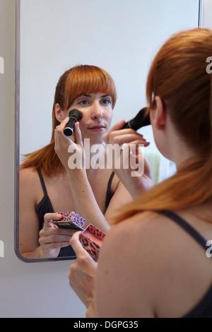 Mitte Erwachsene Frau Anwendung Rouge im Spiegel - Stockfoto