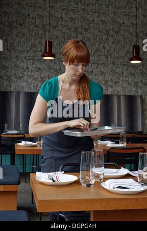Mitte Erwachsene Frau Vorbereitung Tisch im restaurant
