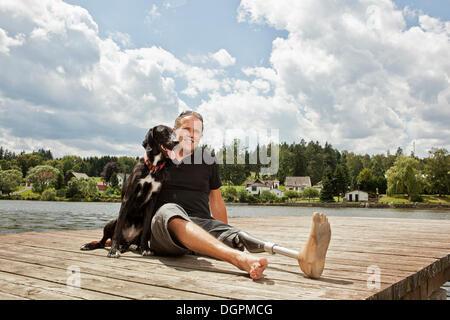 Mann mit einer Beinprothese sitzen auf einem Steg mit seinem Jagdhund - Stockfoto