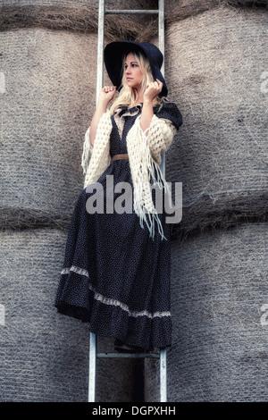 ein schönes Mädchen auf einer Leiter im Heuhaufen - Stockfoto