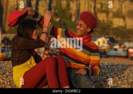 Teenager-Paar sitzt auf einem Kiesstrand an der Hastings UK - Stockfoto