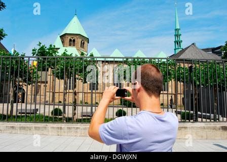Touristen besuchen das Ruhrgebiet, junger Mann die Bilder von der Essener Dom mit einer digitalen Kamera, Kulturhauptstadt - Stockfoto
