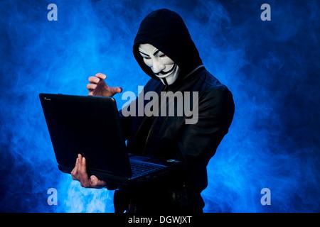 Junger Mann mit einer anonymen Maske mit einer Kapuze und eine schwarze Lederjacke, hält einen laptop - Stockfoto