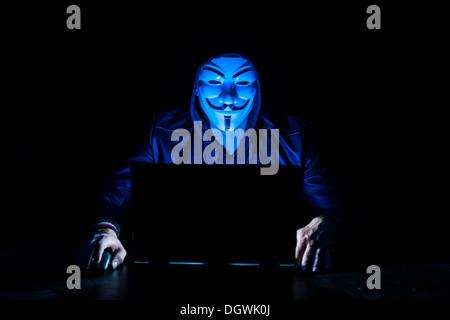 Junger Mann trug eine anonyme Maske und einer Kapuze sitzt vor einem laptop - Stockfoto