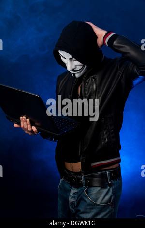 Junge Mann trägt eine anonymen Maske mit Kapuze und eine schwarze Lederjacke, hielt einen Laptop, Scrathing seinen - Stockfoto