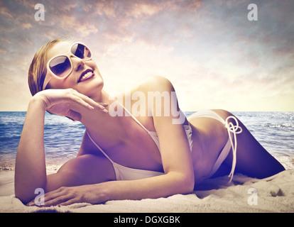 Schöne Frau im weissen Bikini am Strand bei Sonnenuntergang - Stockfoto