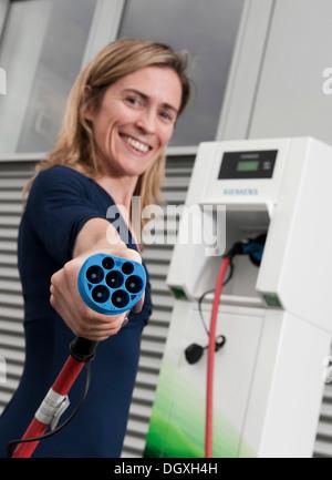 Frau mit einem Ladevorgangs Stecker für ein elektrisches Auto, steht man vor einer Ladestation Charge CP700A von - Stockfoto