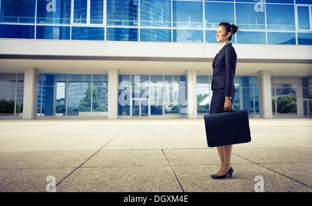 Sekretärin mit einem blauen Kleid stehen in der Nähe von einem modernen Gebäude - Stockfoto