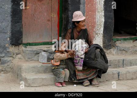 Tibetische Großmutter mit Enkel in der Kloster-Stadt der Sakya vor einem typischen Sakya Hochbau und - Stockfoto